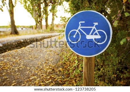 Wooden Post of Bicycle sign on a park. Valladolid, Spain. - stock photo