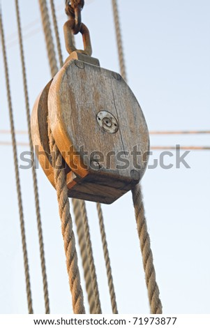 Wooden pulley with ropes against blue sky - stock photo
