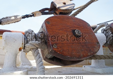 Wooden pulley with ropes on deck  - stock photo