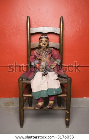 Wooden puppet sitting on chair. - stock photo