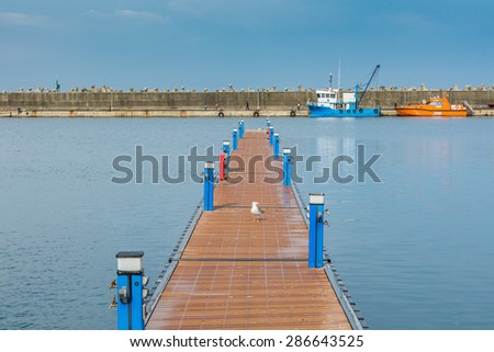 Wooden quay in Constanta touristic harbor over blue sky and two vessels, ships - stock photo