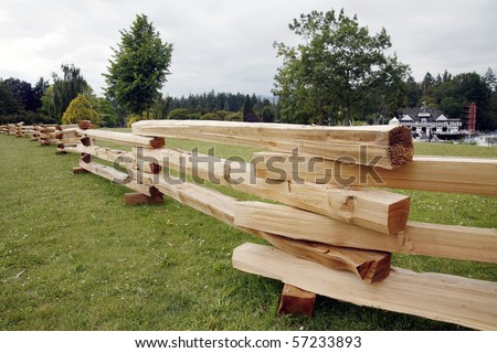 Wooden railing in the park with green grass. - stock photo