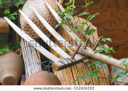 Wooden rake on the background of clay pots and a green plant