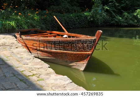 wooden red boat on green water