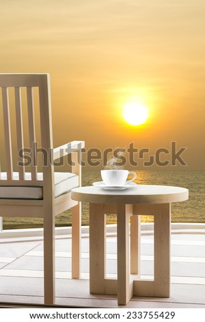 Wooden relax chairs and coffee cup with sunrise on the sea  view background. - stock photo