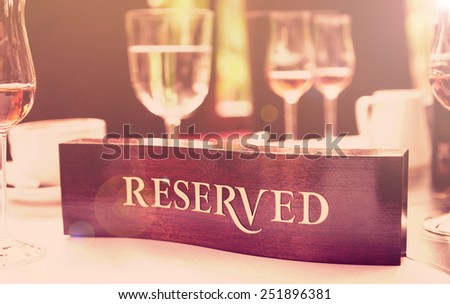Wooden reserved plate on an arranged restaurant table, toned image - stock photo