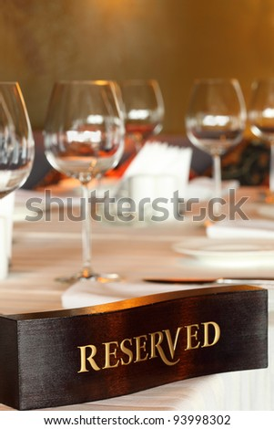Wooden reserved plate on restaurant table with empty dishes and glasses - stock photo