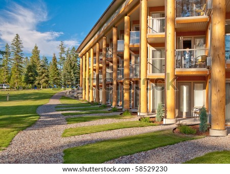 Wooden resort building over trees and gravel paths. - stock photo