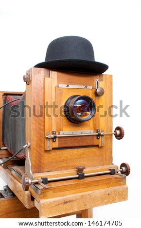 Wooden retro photo camera and bowler hat