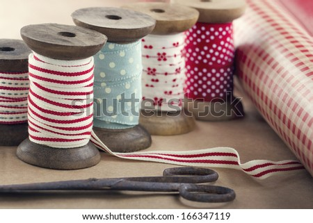 Wooden ribbon spools, paper rolls and old scissors for Christmas present wrapping on brown vintage background - stock photo