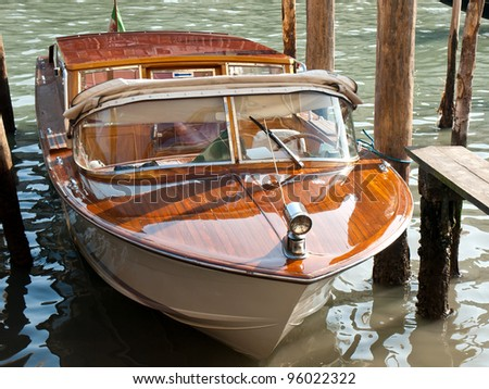 wooden riva boat parked on the canal in Venice - stock photo
