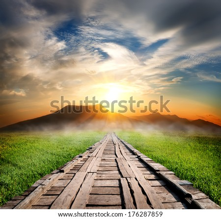 Wooden road in the mountains at sunset