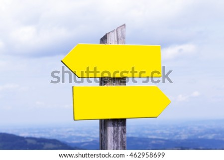 Wooden road pointer over sky and nature landscape background at daylight.