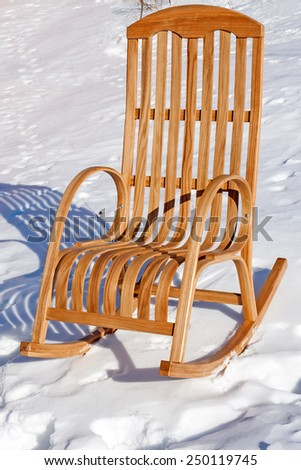 Wooden rocking chair in the snow. Winter sunny day. - stock photo