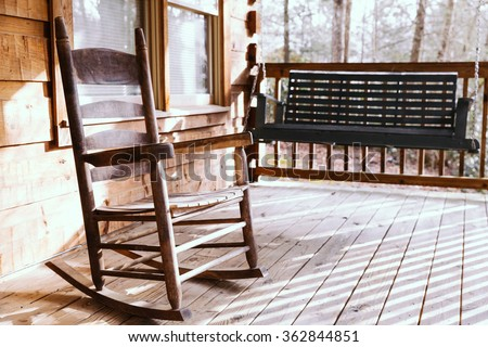 wooden rocking chair on a porch deck of a log cabin with a wooden swing blurred
