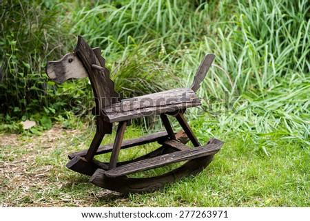 Wooden rocking toy on yard garden. - stock photo