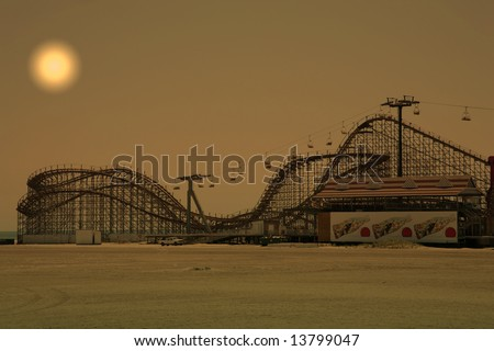wooden roller coaster on beach during sunset hours - stock photo