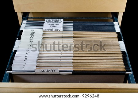 Wooden rolling file cabinet with a drawer opened, showing 43 hanging folders. - stock photo