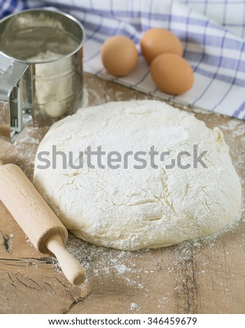 wooden rolling pin with freshly prepared dough