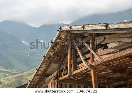 wooden roof gable in front of alpine mountains - stock photo