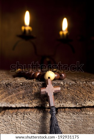 Wooden Rosary Beads and Candles on Wooden Background. - stock photo