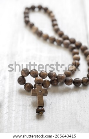 Wooden rosary beads and cross on wooden background - stock photo