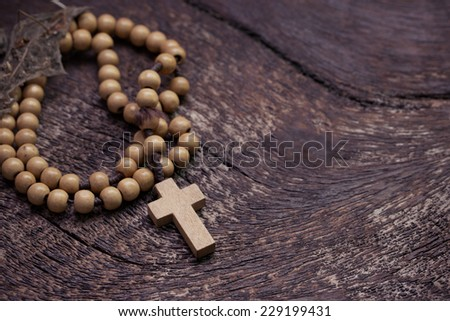 Wooden rosary beads on old wooden background - stock photo