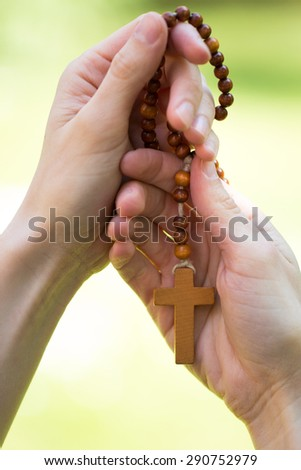 Wooden rosary in woman hands - stock photo