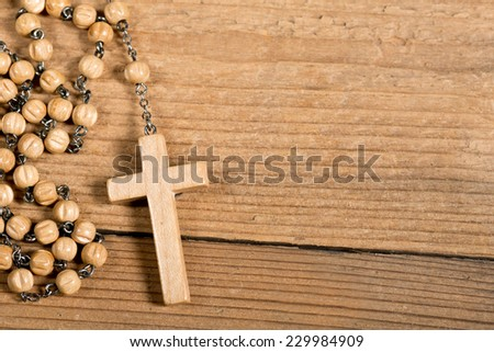 wooden rosary on th old wooden desk - stock photo