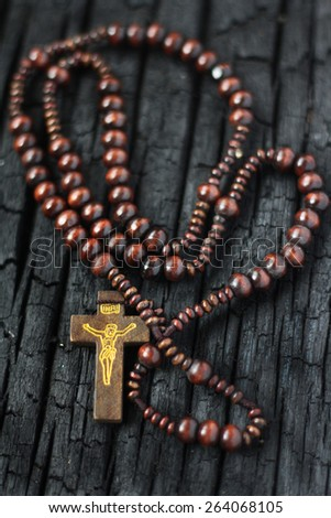 wooden rosary on the burn wooden  - stock photo