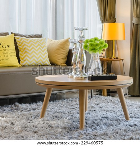 wooden round table on carpet in modern living room - stock photo