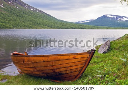Wooden rowboat at Lapland lake in summer. - stock photo