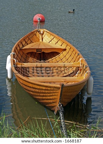 Wooden rowing boat in a bay - stock photo
