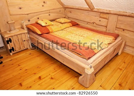 Wooden rustic bed in country cottage bedroom. - stock photo