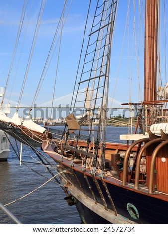 Wooden sail boat moored to docks on the Savannah river with Talmadge bridge in the background