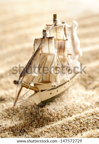 wooden sail ship toy model in the sea sand close-up. Shallow depth of field - stock photo