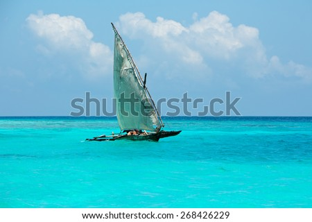 Wooden sailboat  (dhow) on the clear turquoise water of Zanzibar island - stock photo