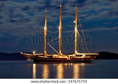 Wooden sailboat illuminated at night anchored - stock photo