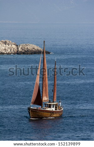 Wooden sailboat sails near coast of island Brac, Croatia - stock photo