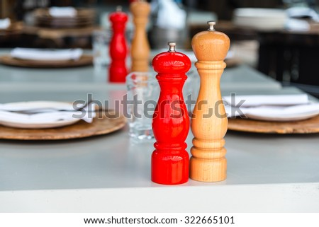 wooden salt and pepper mill on a set table - stock photo