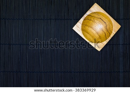 Wooden Sauce cup on the black bamboo mat background in top view - stock photo