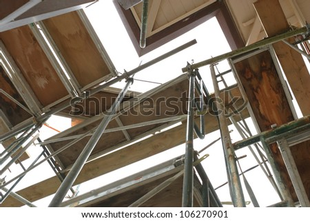 Wooden scaffolding of a construction site - stock photo