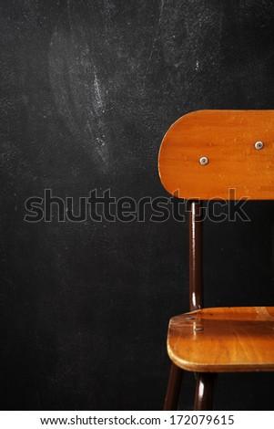Wooden school chair against blackboard - stock photo