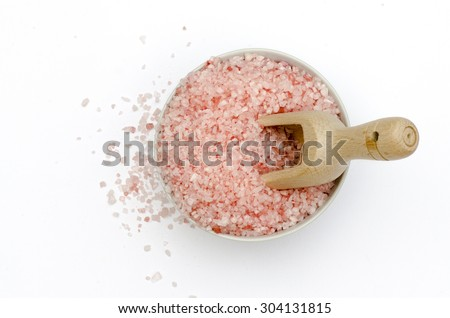 wooden scoop, bowl full of bath salts with pink and white grains for spa - stock photo