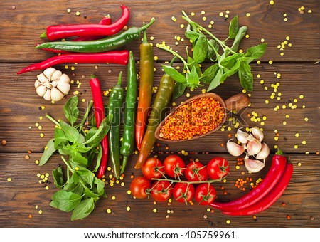 Wooden scoop of orange lentils with red and green hot chilli peppers and tomatoes, onion and basil leaves on a wooden background - stock photo