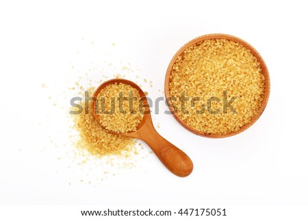 Wooden scoop spoon and bowl full of brown cane sugar with pinch of sugar spilled around isolated on white background, top view