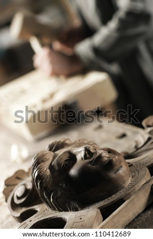 wooden sculpture, the master on the background - stock photo