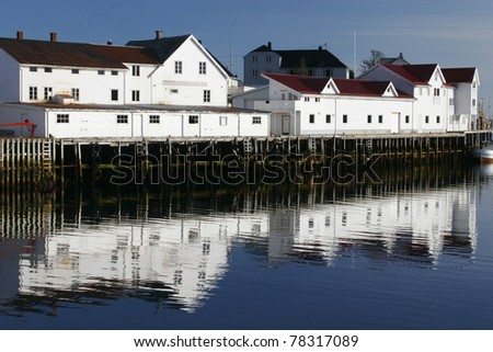 Wooden seaside houses standing on pillars over the water in summer, Norway.