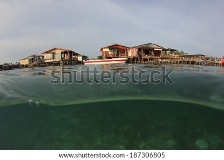 Wooden Seaside Longhouses on tropical island, at risk from global warming and rising sea levels - stock photo