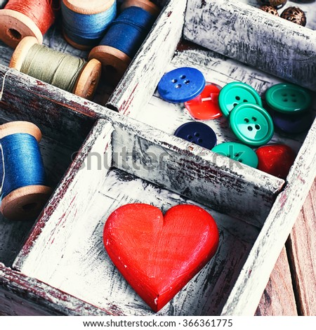 Wooden sewing box with threads,buttons and symbolic heart - stock photo